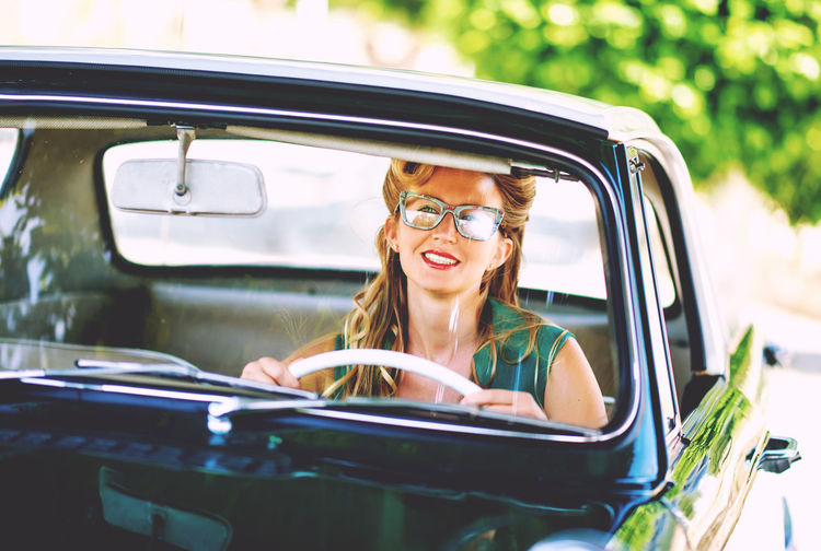 Beautiful happy woman sitting in a car. Retro styled Bright Colors Driving Happiness Sitting Summertime Sunlight Woman Beautiful Woman Blond Hair Drive Eyeglasses  Journey One Person Outdoors Retro Car Retro Style Retro Styled Smiling Spectacle Summer Sunny Day Vintage Vintage Car Young Adult Young Women