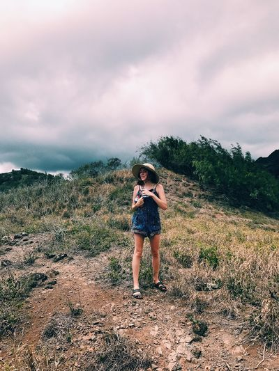 Full length of woman standing on mountain against sky