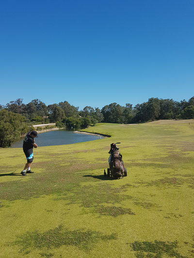 Friends on golf course against clear blue sky