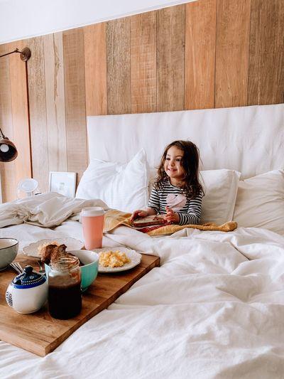 Full length of little girl sitting on bed having breakfast