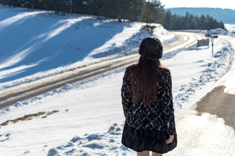 Winter Snow Cold Temperature One Person Clothing Leisure Activity Rear View Land Lifestyles Nature Day Warm Clothing Real People Focus On Foreground Women Sunlight Beauty In Nature Adult Outdoors Hairstyle