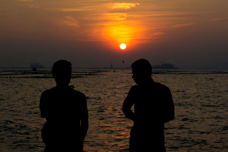 Rear view of silhouette friends standing at beach during sunset