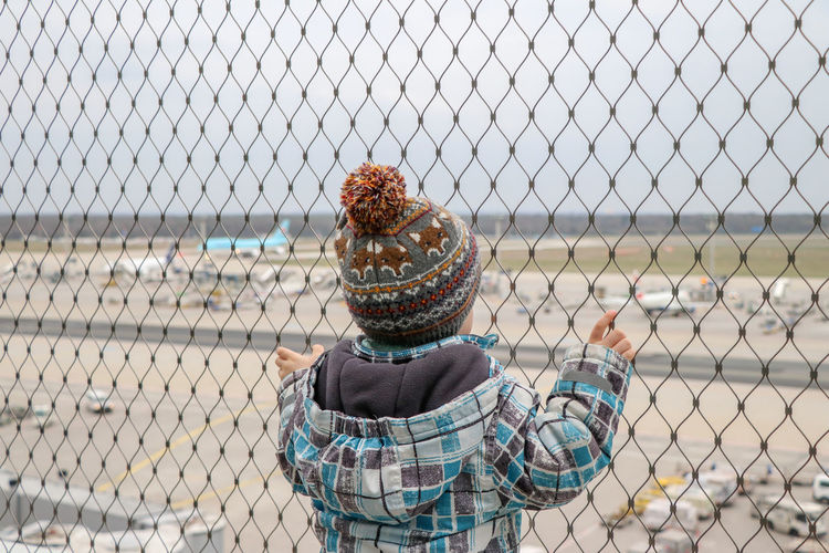 Fence Day One Person Outdoors Focus On Foreground Real People Chainlink Fence Security Metal Safety Sky Holding Airport Plane Rear View Warm Clothing Protection Pattern Airplane Air Vehicle Fascinating Child Childhood Transportation Travel Traveling Airport Runway Airport Terminal Terminal View EyeEm Best Shots Barrier