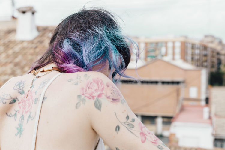 Rear view of woman with tattoo against buildings and sky