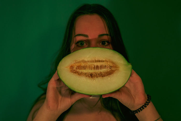 Portrait of woman holding melon against wall