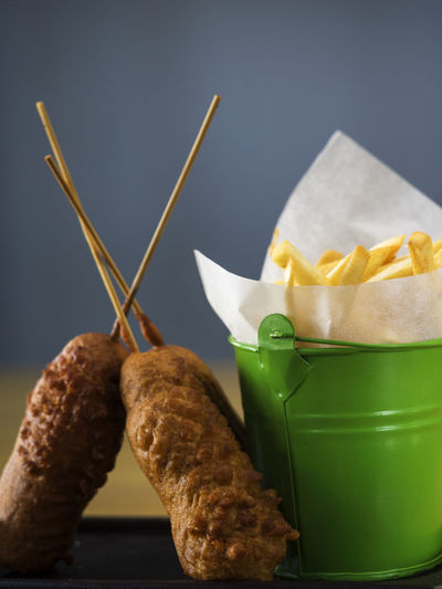 Close-up of corn dogs with french fries served on table
