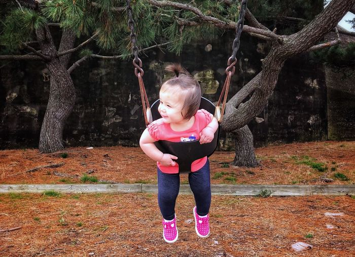 Happy girl playing on swing in park