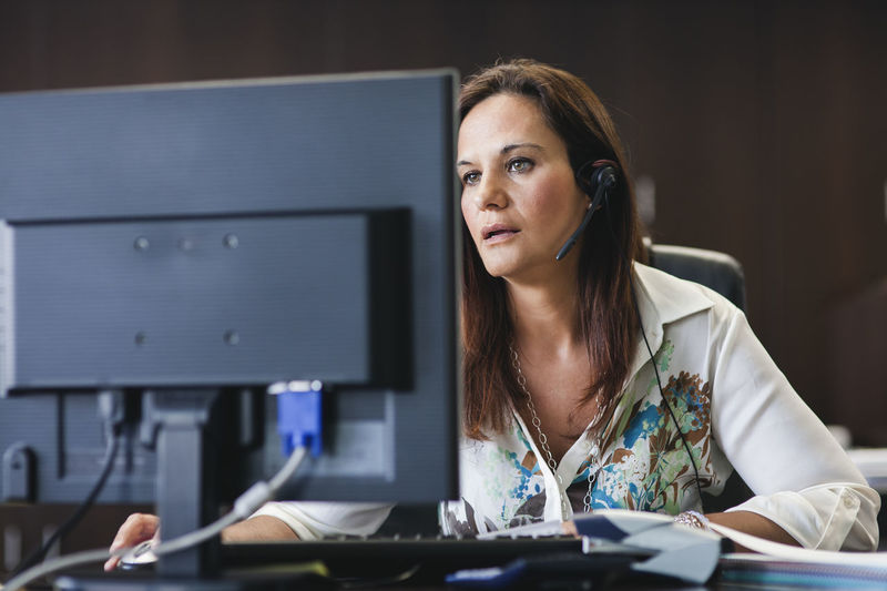 call center operator woman working in office with headphones and computer Adult Business Business Person Businesswoman Computer Desk Furniture Headshot Indoors  Occupation Office One Person Portrait Sitting Table Technology Using Computer Women Working