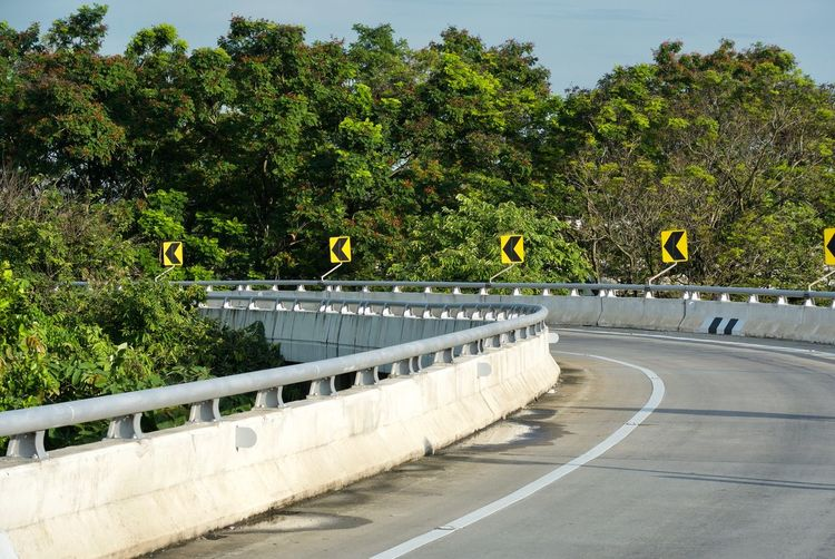 Architecture Built Structure City Concrete Day Direction Empty Green Color Growth Nature No People Outdoors Plant Railing Road Road Marking Sign Symbol The Way Forward Transportation Tree