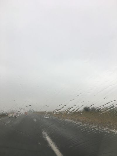 Rainy day on the road Weather Cloudy Wet Sky Road Water No People Nature Transportation Rain Day Drop Motor Vehicle Copy Space Glass - Material Car Mode Of Transportation Transparent Land Vehicle Vehicle Interior Outdoors Rainy Season
