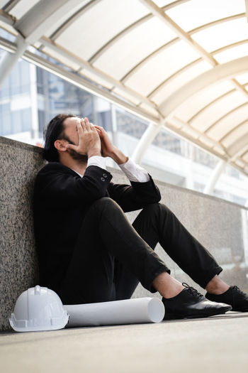 Stress Adult Business Business Person Businessman Contemplation Day Depression - Sadness Engineering Failure  Formalwear Hand Helmet Job Males  Men Office One Person Real People Sadness Sitting Unemployed Well-dressed Young Adult Young Men