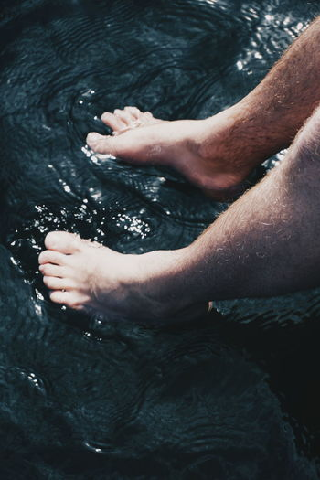 Low section of man sitting in water