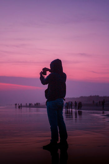 Silhouette man photographing by lake against sky during sunset
