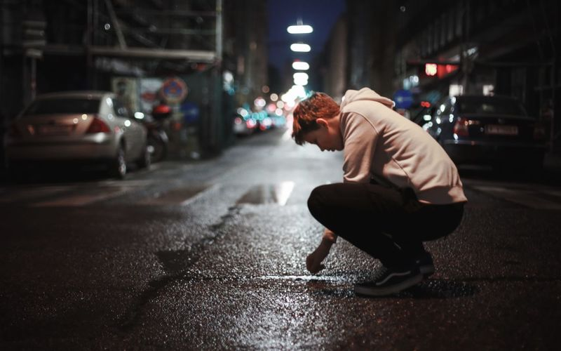 Close-up Street Real People Night Full Length One Person Lifestyles Transportation Road Side View Crouching Illuminated Men Outdoors City Young Adult Adult People Blond Hair The Portraitist - 2017 EyeEm Awards One Young Man Only Portrait