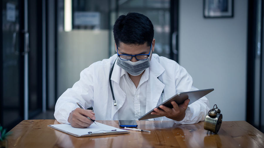 Doctor wearing mask writing on note pad at clinic