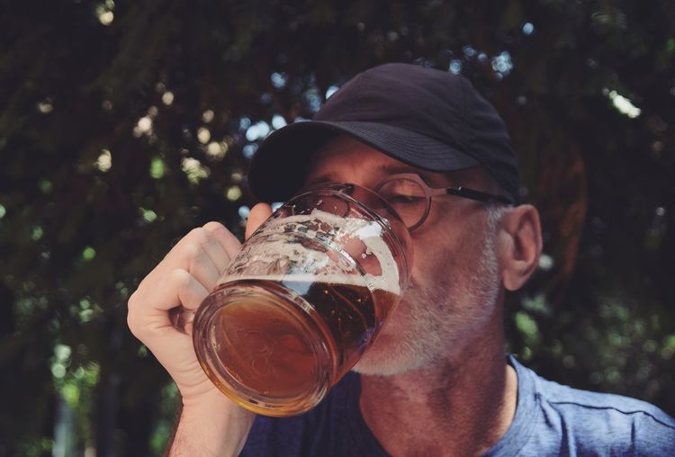 Man drinking beer in glass against tree