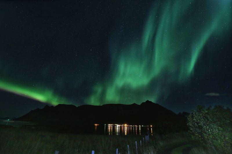 Scenic view of aurora borealis over mountain at night
