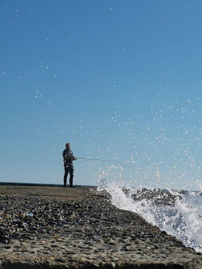 Full length of man fishing in sea while standing against clear sky