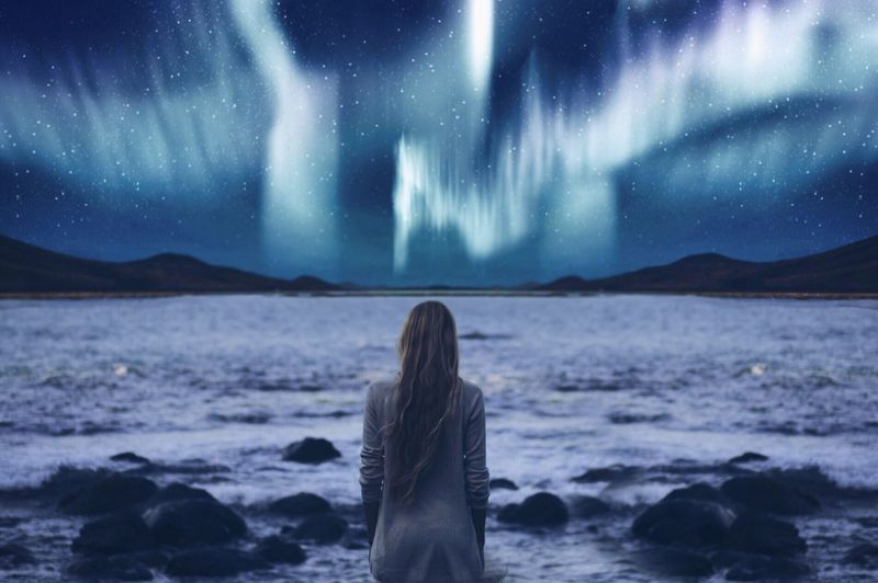 Rear view of woman looking at sea and star filled sky