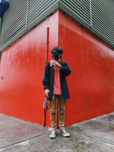 Full length of man standing against red wall