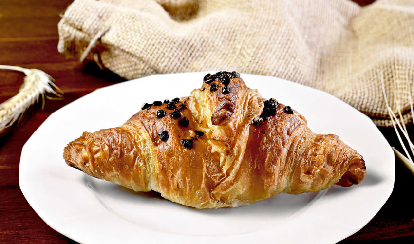 Chocolate croissant on a wooden table with linen fabric and ear of breakfast scene. Breakfast Wooden Table Baked Breakfast Chocolate Croissant Close-up Croissant Dessert Focus On Foreground Food Food And Drink French Food Freshness Indoors  Indulgence Linen No People Plate Ready-to-eat Serving Size Snack Still Life Sweet Sweet Food Table