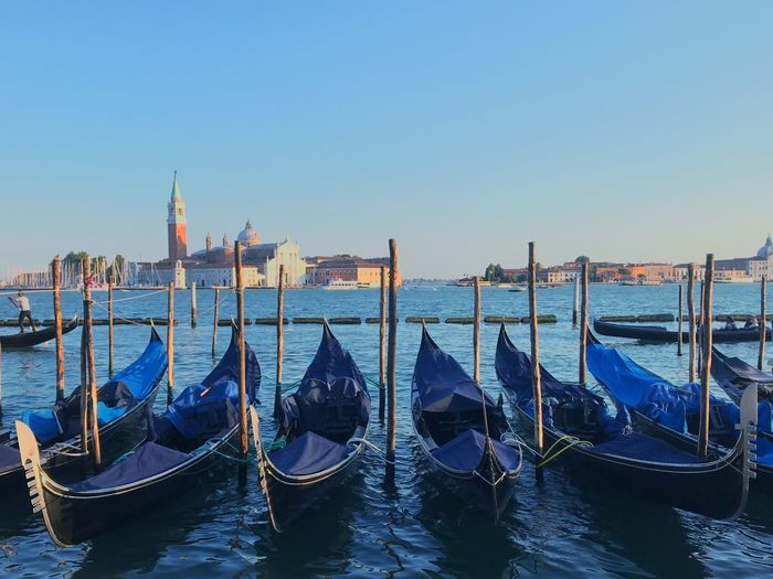 Gondolas moored at canal against clear sky