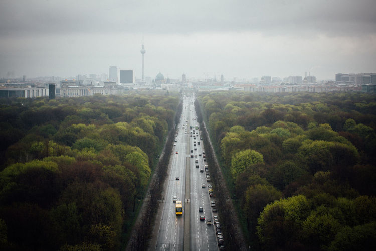 City Street Amidst Trees Leading Towards Fernsehturm In City Against Cloudy Sky