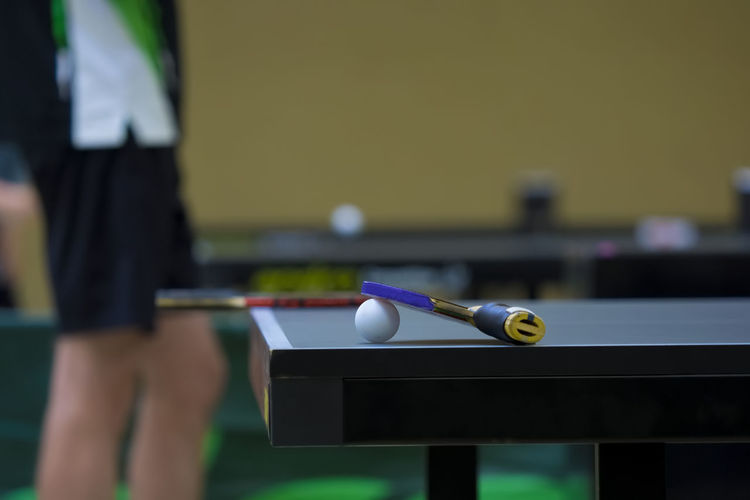 Close-up of table tennis racket and ball on table with person in background