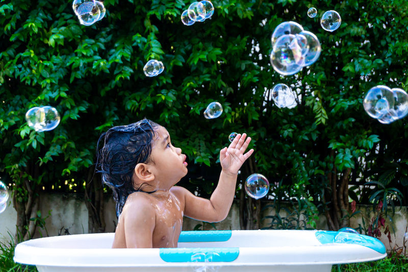 Full length of shirtless boy with bubbles