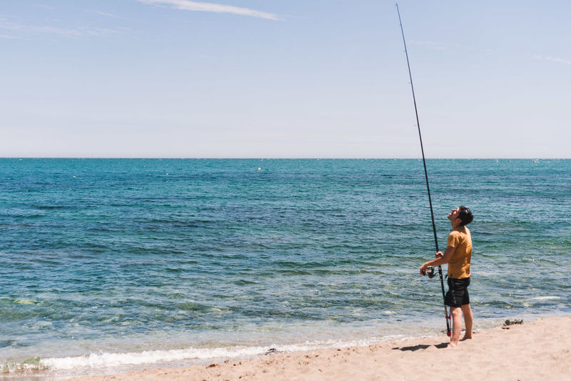 Full length of man fishing on sea against sky