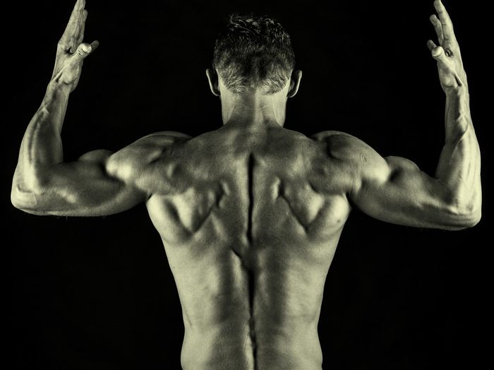 Low angle view of shirtless man against black background
