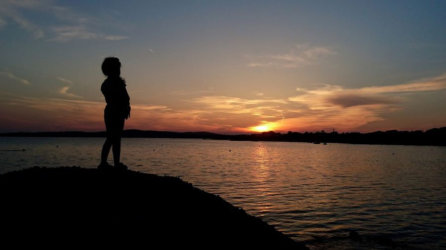 Silhouette boy standing on beach against sky during sunset