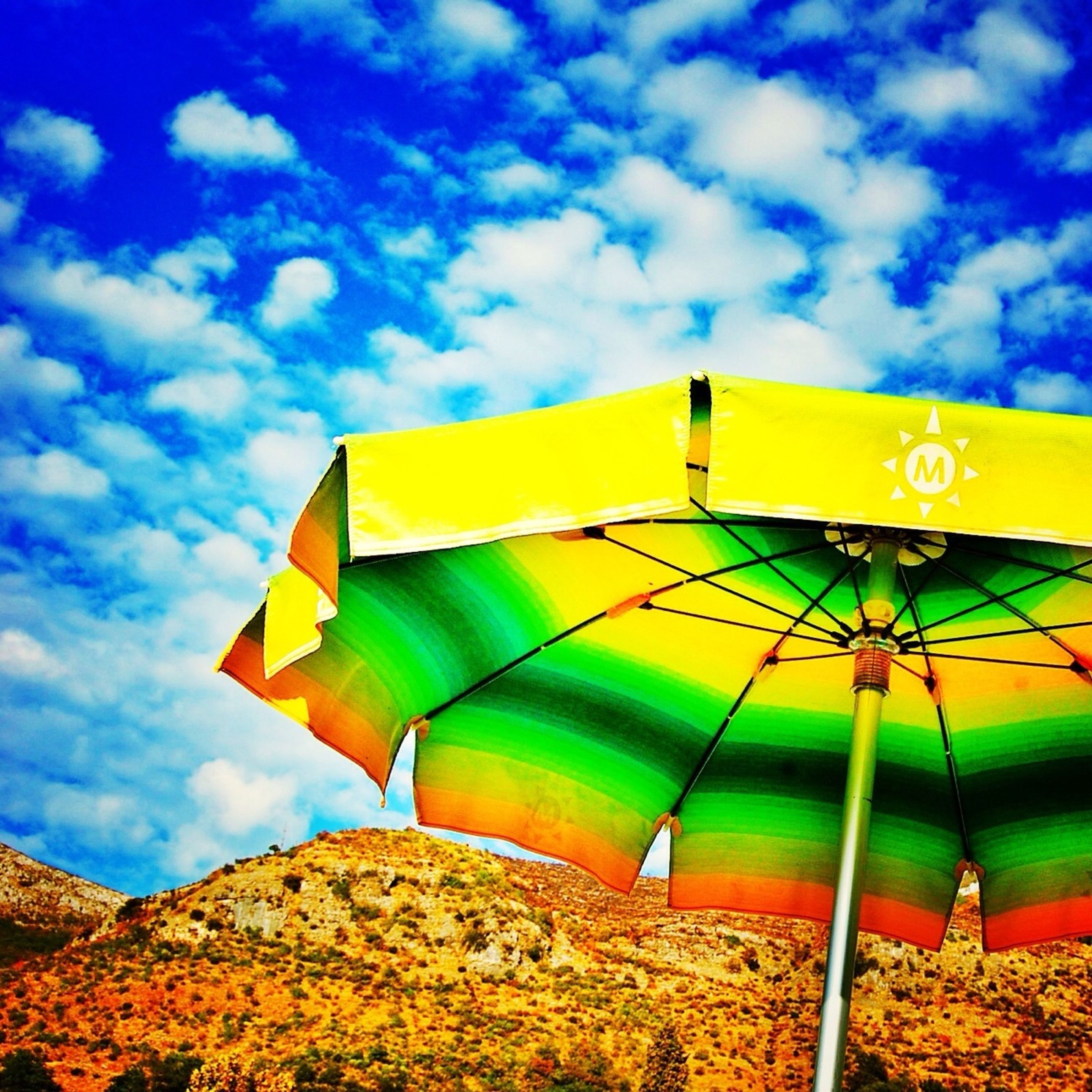 sky, yellow, cloud - sky, cloud, low angle view, umbrella, cloudy, nature, multi colored, flag, blue, tent, protection, outdoors, tranquility, built structure, day, beauty in nature, parasol, scenics
