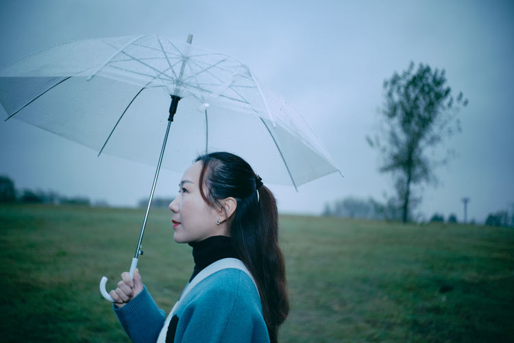Side view of woman holding umbrella on land