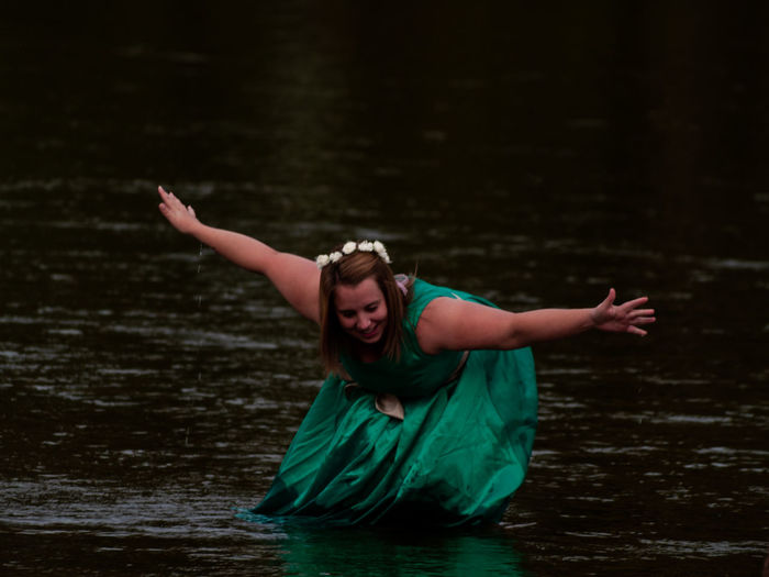 Woman with arms outstretched in river