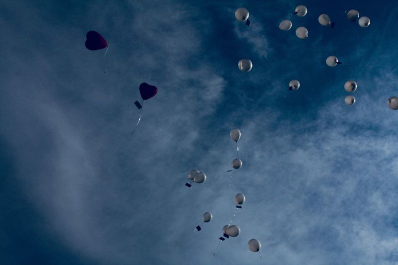 Low angle view of balloons flying in blue sky