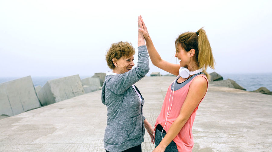 Mother and daughter standing on pier against sky