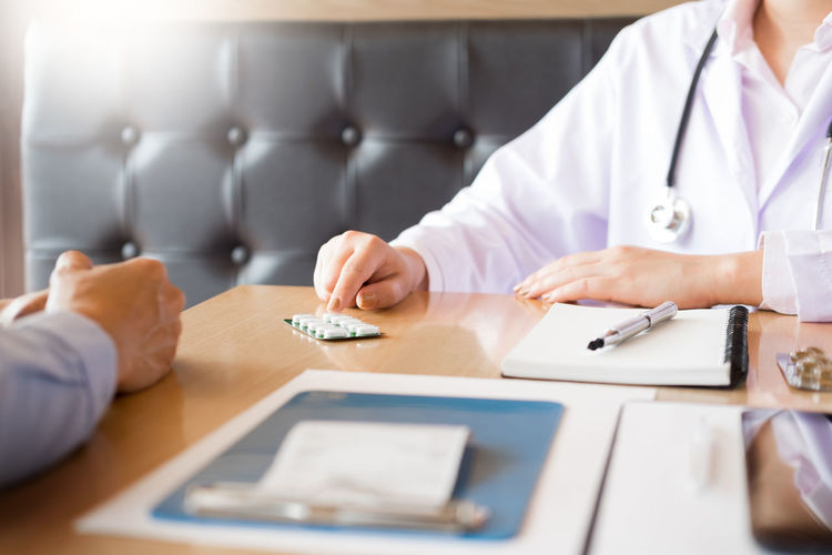 Midsection Of Doctor Pointing At Medicine While Patient Sitting On Table In Hospital