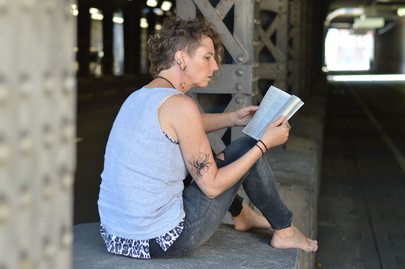 Mature woman reading bible in underpass