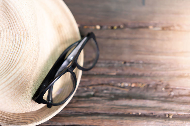 Eyeglasses and hat on wooden background Accessories Accessory Background Beach Black Closeup Color Concept Copy Creative Decoration Design Eye Eyeglasses  Fashion Flat Frame Glasses Hat Holiday Isolated Lay Modern Natural Object Old Protection Reflection Retro Rustic Sea Space Spectacles Straw Style Stylish Summer Sun Sunglasses Sunlight Table Texture Top Travel Vacation View Vintage White Wood Wooden
