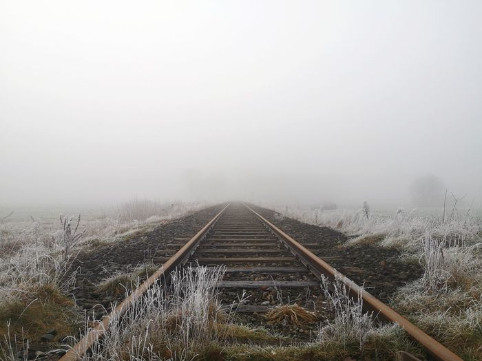 Railroad tracks on field against sky during winter