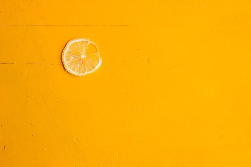 Lemon slice on a yellow table Lemon SLICE Yellow Table Background Backgrounds Bright Fruit Citrus