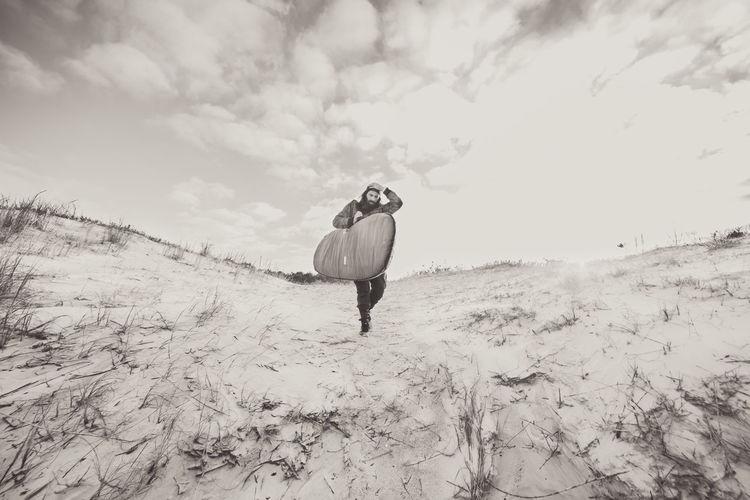 Man with surfboard walking on landscape against sky