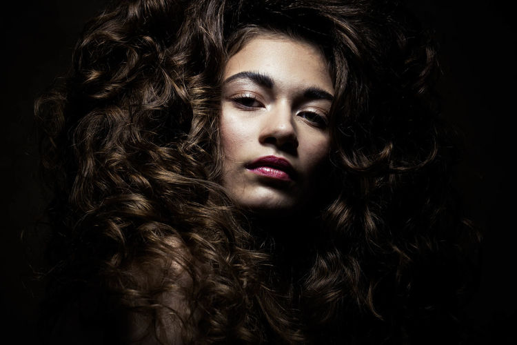 Adult Adults Only Beautiful People Beautiful Woman Beauty Black Background Brown Hair Close-up Curly Hair Front View Human Body Part Make-up One Person One Woman Only One Young Woman Only Only Women People Portrait Shiny Stage Make-up Studio Shot Women Young Adult Young Women