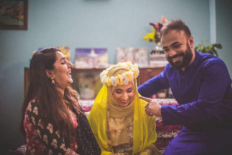 Smiling friends with bride in home