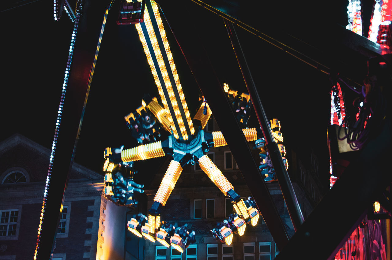 LOW ANGLE VIEW OF ILLUMINATED FERRIS WHEEL AGAINST BUILDINGS