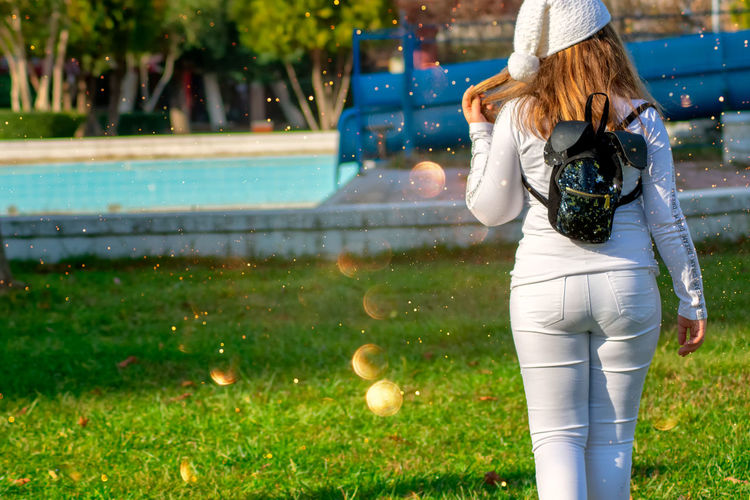 Full length of woman photographing on grass