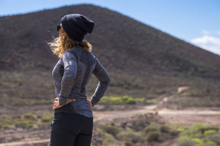 Curly woman viewed from rearoking the way and stand in the outdoor natural place- hiking equipment and sport active lifestyle for active people - trekking concept for female Leisure Activity Three Quarter Length Clothing Lifestyles One Person Hat Real People Women Rear View Standing Nature Adult Young Adult Day Young Women Land Casual Clothing Focus On Foreground Hair Hairstyle Outdoors Females Caucasian Footpath Mountain Excursion People person Curly Hair Enjoying Life Breathtaking Adventure Desert Arid Climate Tropical Climate Standing Sport Activity Active Healthy Lifestyle