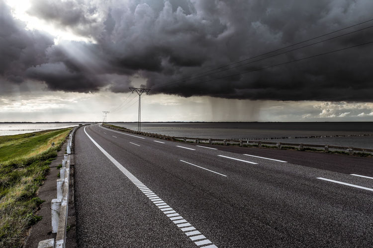 Beauty In Nature Cloud - Sky Diminishing Perspective Direction Dividing Line Dramatic Sky Empty Road Marking Nature No People Ominous Outdoors Overcast Road Road Marking Sign Sky Storm Storm Cloud Symbol The Way Forward Transportation