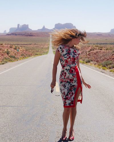 Woman standing with hair blowing in front of monument valley desert